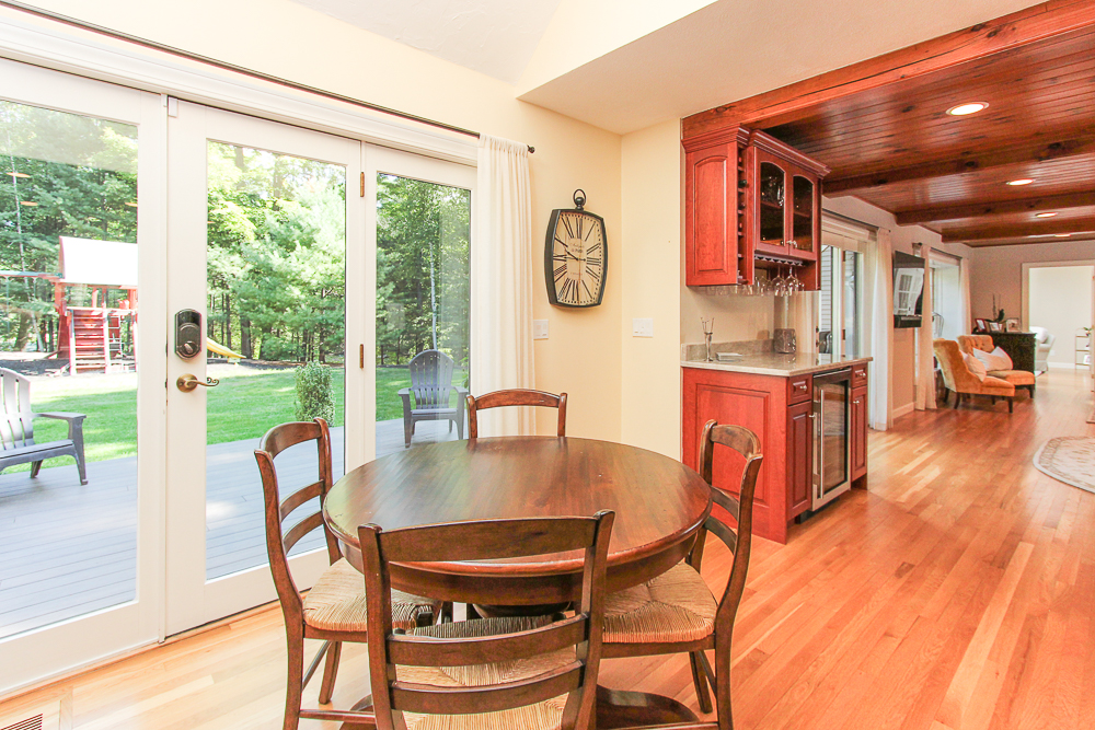 Kitchen dining area, glass doors to the deck, family room in the background at 48 Boren Lane Boxford Massachusetts