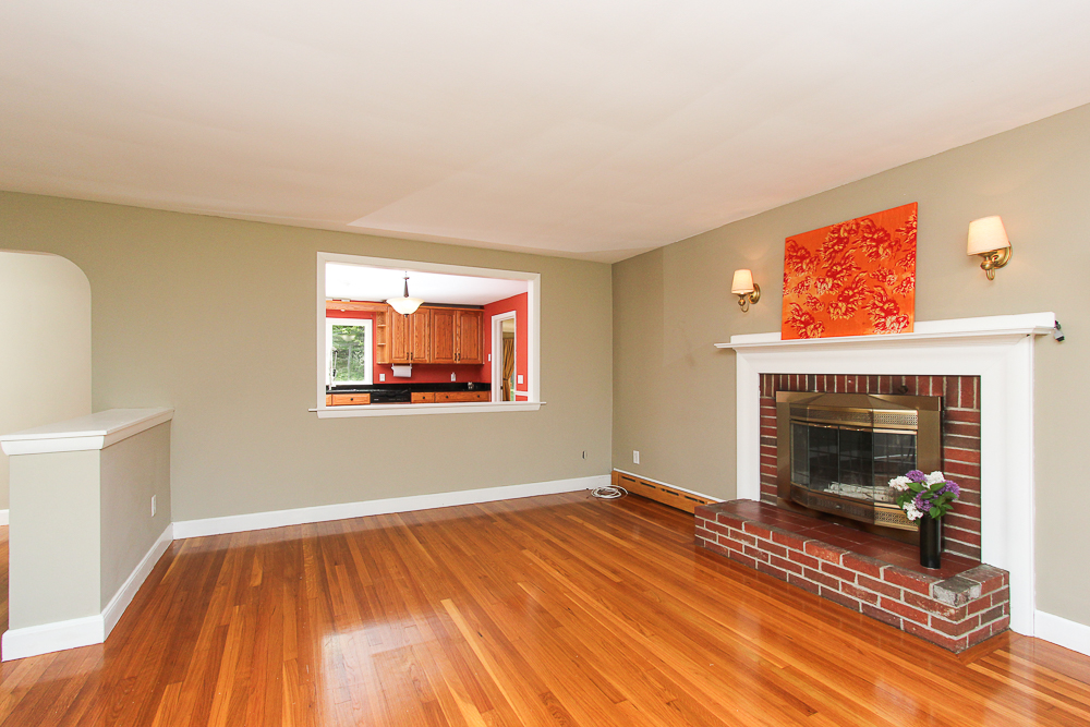 Living room with fireplace and window to kitchen 101 Maple Street Wenham Massachusetts