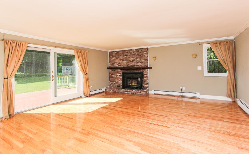 Family room with fireplace hardwood floors nd sliders to the deck 101 Maple Street Wenham Massachusetts