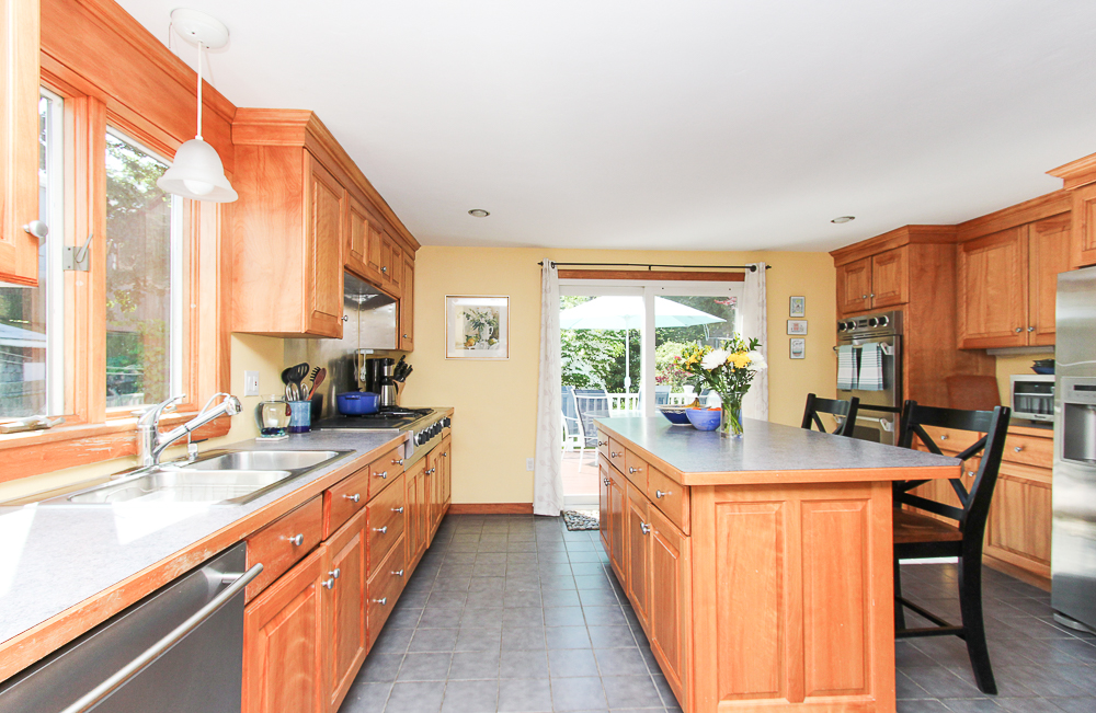 Kitchen with island and breakfast bar and glass sliding doors leading to deck 18 Hobart Avenue Beverly Massachusetts
