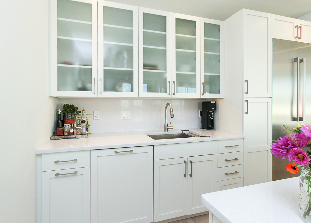 White cabinets with glass fronts in the kitchen at 266 Merrimac Street Newburyport Massachusetts - Unit D