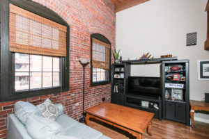 Living room with brick wall and two large windows