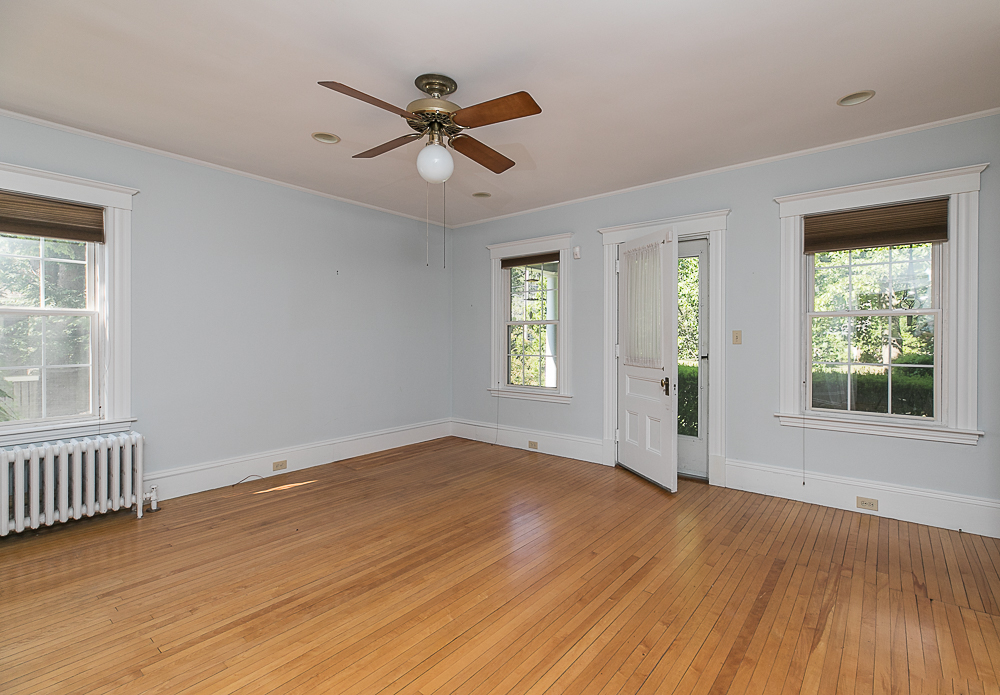 Family room with ceiling fan and hardwood floors and front foor at 38 Arbor Street Hamilton Massachusetts