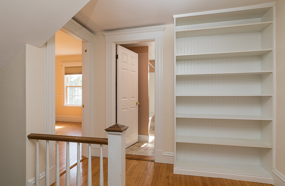 Second floor hallway with built-in book shelves at 38 Arbor Street Hamilton Massachusetts