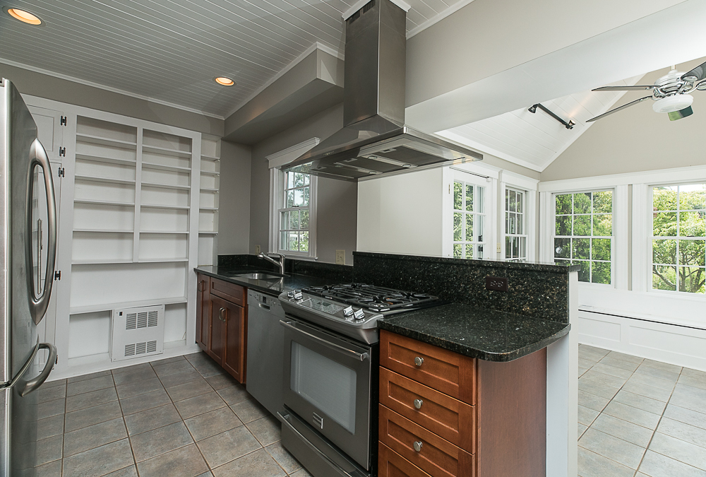 Kitchen with granite counters and stainless steel appliances at 38 Arbor Street Hamilton Massachusetts